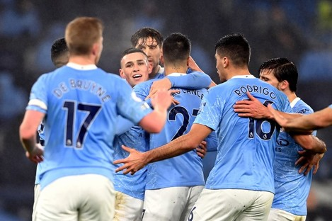 The Manchester City players hug Phil Foden after his goal last night.