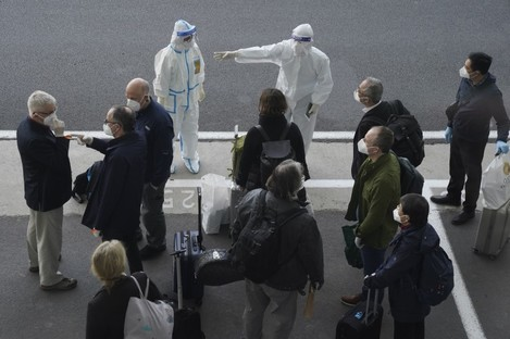A worker in protective coverings directs members of the WHO team on their arrival at the airport in Wuhan.