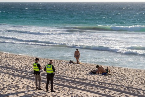 Police officers patrol Scarborough Beach in Perth just after a lockdown was announced today.