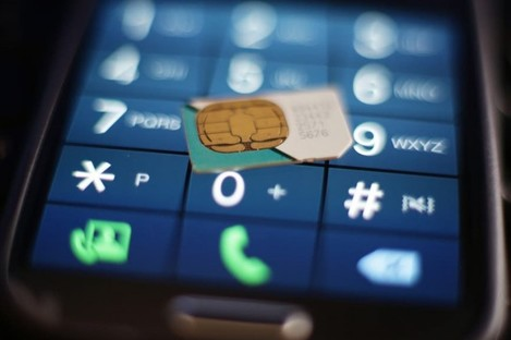 File photo of a mobile phone and SIM card