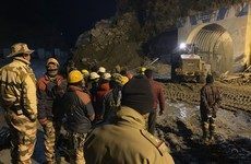 Indian rescuers begin drilling debris-filled tunnel in bid to reach dozens of people trapped inside