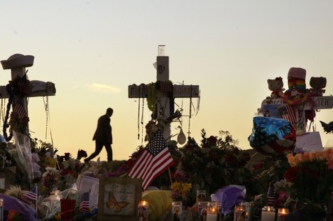 A man walks on a hill near crosses set up at the memorial to victims of the Aurora, Colo., movie theater shooting, early Friday, July 27, 2012