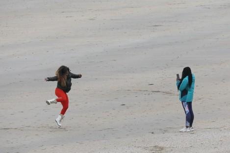 A woman jumps for a photograph taken by a friend on the beach in Ballbriggan, Dublin.