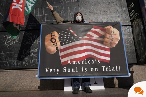 A protester holds a sign across the street from the Hennepin County Government Center Tuesday, April 6, 2021, in Minneapolis where testimony continues in the trial of former Minneapolis police officer Derek Chauvin. Chauvin is charged with murder in the death of George Floyd during an arrest last May in Minneapolis. (AP Photo/Jim Mone)