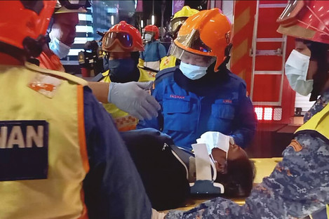 Rescuers transferring a passenger injured in a metro train collision in Kuala Lumpur, Malaysia today.