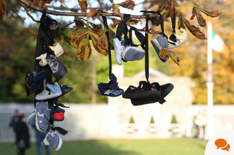 Baby shoes tied to a tree during a Mother and Baby Home protest event at Áras an Uachtaráin
