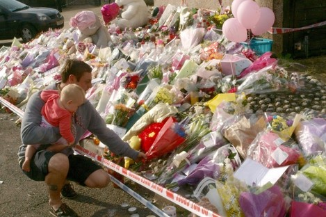 A man lays flowers at a memorial for Tia Sharp near her grandmother's home