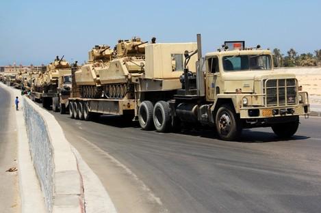 Army trucks carry Egyptian military tanks in El Arish, Egypt's northern Sinai Peninsula, Thursday, Aug. 9, 2012