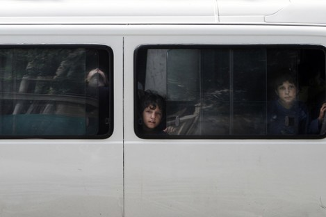 Afghan children look out of a bus window in Kabul today.