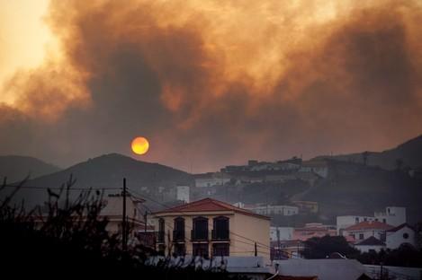 Smoke billows across houses as a wildfire burns near Chipude Village, La Gomera, Spain