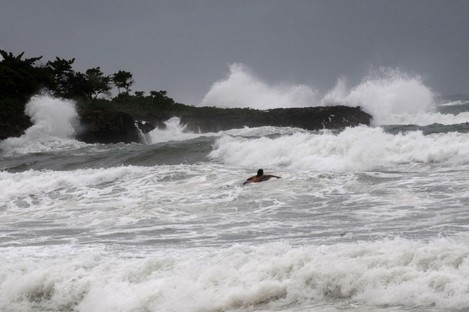 A surfer swims out to sea at Manresa beach as Tropical Storm Isaac approaches Santo Domingo, Dominican Republic
