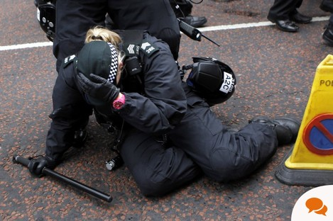 A female police officer knocked to the ground last Saturday in scuffles after loyalist bands marched past a Catholic church in Belfast while playing music that was banned by the Parades Commission.