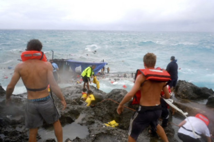 People clamber on the rocky shore on Christmas Island during a rescue attempt as a boat breaks up in the background this morning.