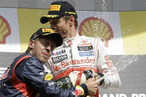 McLaren Mercedes driver Jenson Button of Britain, winner, top, celebrates sprays champagne with second place Red Bull driver Sebastian Vettel of Germany.