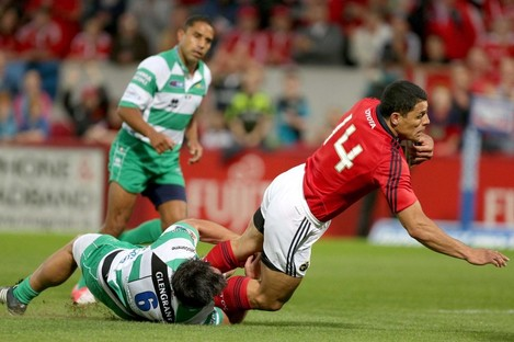 Munster's Doug Howlett scores the first try despite the attenions of Treviso's Simone Favaro.