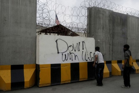 A Pakistani protester spray paints on the wall of the US consulate during a demonstration in Karachi, Pakistan, on Sunday