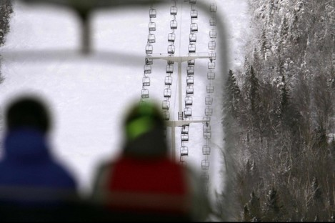 Skiers ride a chairlift with a view of Spillway East chair lift, background, where six people were injured when five chairs fell to the ground yesterday.