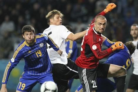 Kazakhstan's Viktor Dmitrenko, left, Austria's Sebastian Prodl, center, and Kazakhstan's goalkeeper Sergei Ostapenko, right, struggle for the ball.
