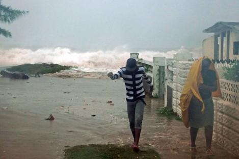 Residents evacuate their home as waves crash in the Caribbean Terrace neighborhood of eastern Kingston, Jamaica on Wednesday