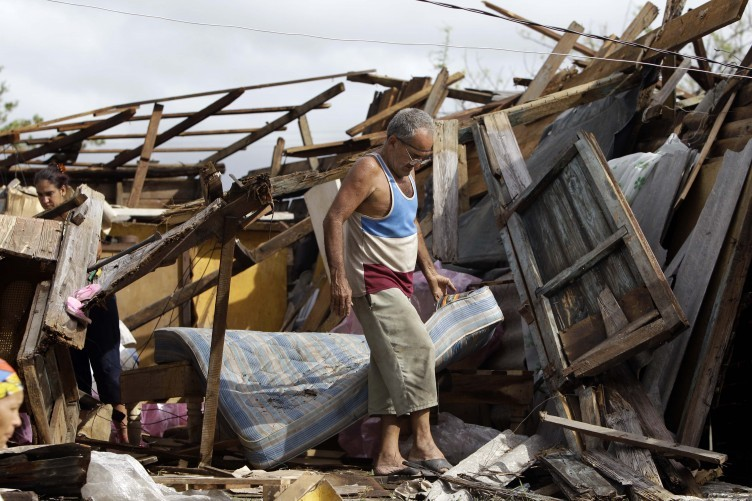 Resident Antonio Garces tries to recover his belongings from his house destroyed by Hurricane Sandy in Aguacate, Cuba, Thursday Oct. 25, 2012