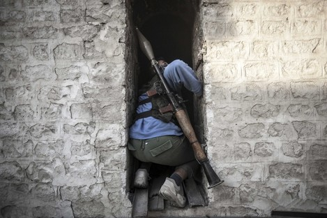 A rebel fighter takes cover as he looks back up at a warplane attacking rebel positions during heavy clashes between rebel fighters and the Syrian army.