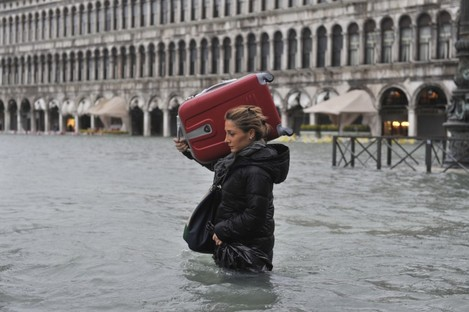 A tourist crosses flooded St. Mark's Square in Venice, Italy, today.