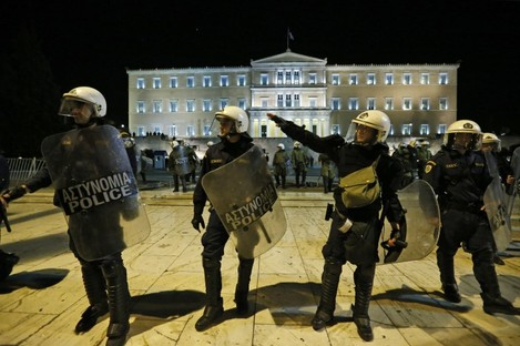 Greek riot police officers move to push anti austerity protesters off the street, in front of the Parliament in central Athens yesterday.