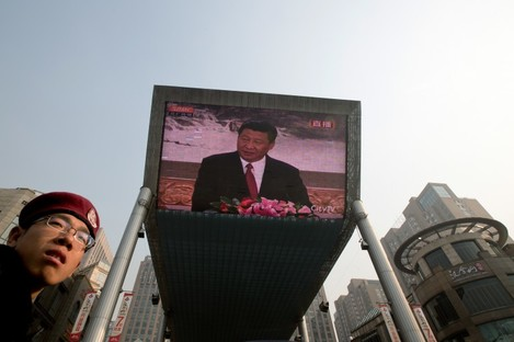 A security guard stands near a huge screen showing a live broadcast of China's new Communist Party General Secretary Xi Jinping speaking during a press event earlier today.