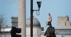 Naked man scales London statue