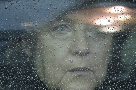 German Chancellor Angela Merkel looks out from behind raindrops on her car window as she arrives for an EU summit in Brussels