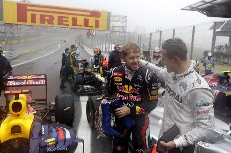 Michael Schumacher (right) congratulates Sebastian Vettel on his achievement.