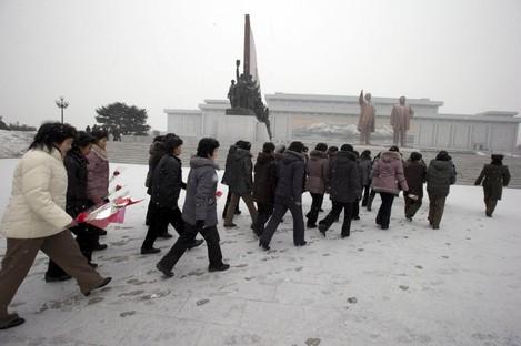 North Koreans walk by statues of former leaders in Pyongyang earlier today