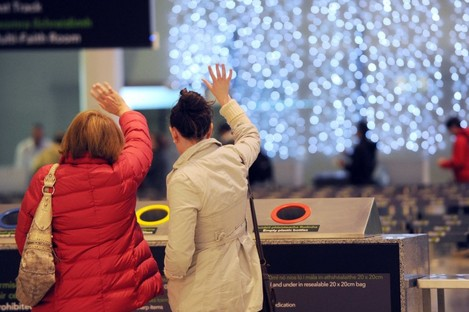 People wave goodbye to family and friends at Dublin Airport as they leave Ireland after the festive break