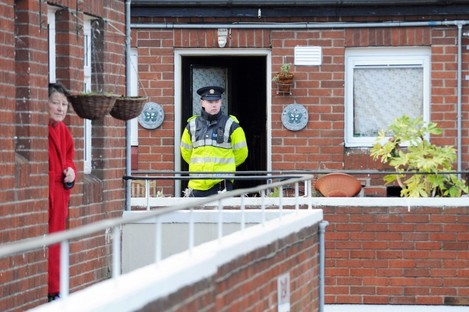 A garda stands watch outside the house in Stoneybatter where the couple were found dead this lunchtime.