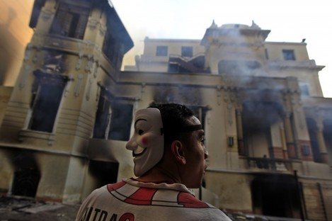 An Egyptian protester stands next to a burning school building during clashes between protesters and riot police near Tahrir Square in Cairo yesterday