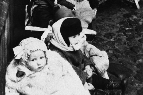 Heavily clothed for protection against the bitter weather, Russian children take cover in an air raid shelter in a public park in Leningrad, Russia, during a raid by Nazi planes: 18/04/1942.