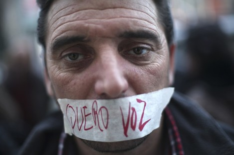 "Portuguese worker Luis Silva at an anti-austerity protest last month. The tape over his mouth reads: ""I want a voice""."