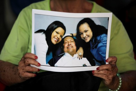 A woman holds a print of one of the photographs of Chavez released by the Venezuelan government on Friday