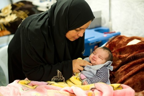 A mother cares for her child at a Red Cross Red Crescent field hospital in Mafraq, Jordan