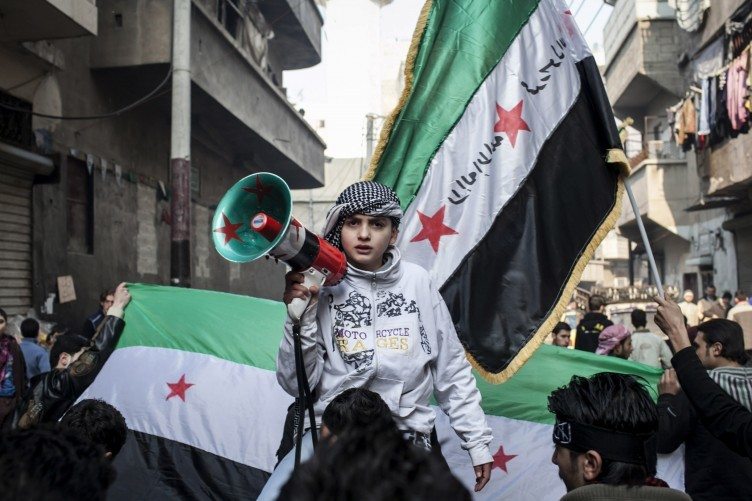 A child uses a megaphone to lead others in chanting Free Syrian Army slogans during a demonstration in the neighborhood of Bustan Al-Qasr, Aleppo, Syria