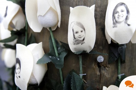 Pictures of Newtown shooting victims are imprinted on fake roses at a memorial in the Sandy Hook village of Newtown.