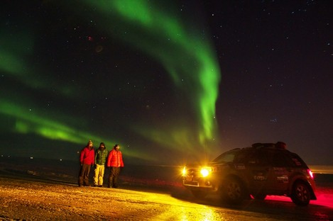 The trekkers watching the Northern Lights by their jeep
