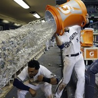 Perfectly-timed photo of a baseball player ducking a post-match soaking