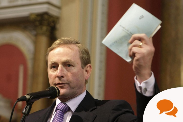 Taoiseach Enda Kenny holds a copy of the Constitution