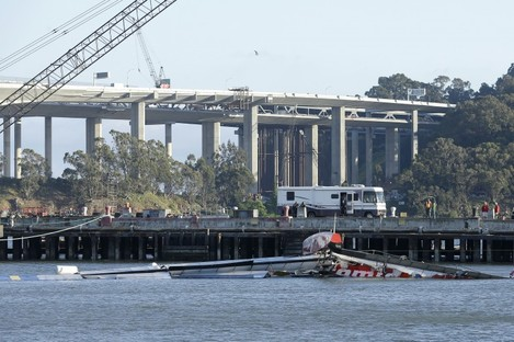 The Artemis Racing AC72 catamaran, an America's Cup entry from Sweden, lies capsized near the Oakland-San Francisco Bay Bridge.
