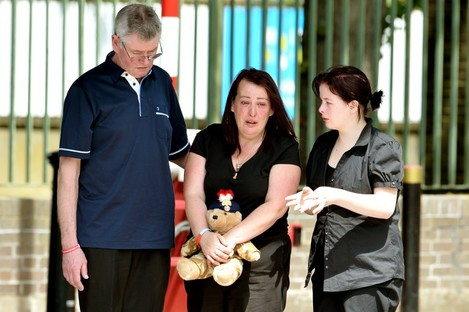 Lyn Rigby, mother of Drummer Lee Rigby, holding a teddy bear joins other family members as they look at floral tributes outside Woolwich Barracks as they visited the scene of his murder in Woolwich, south-east London yesterday.