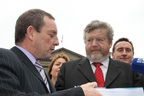 Jerry Buttimer gives James Reilly his committee's report following its first hearings in January. A second report, extending to over 1,600 pages, has been handed over today.