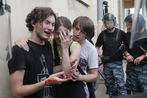 Riot police guard gay rights activists who have been beaten by anti-gay protesters during a rally in St Petersburg in Russia yesterday