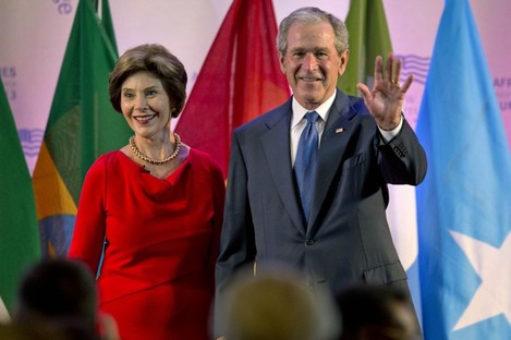 """George W Bush on stage with his wife at the """"First Ladies Summit"""""""