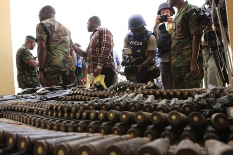 June 5, 2013 file photo, journalists look at arms and ammunition which military commanders say they seized from Islamic fighters, in Maiduguri, Nigeria.